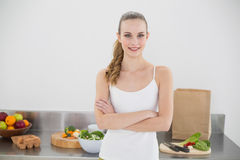 Pretty smiling woman standing cross-armed. In bright kitchen Royalty Free Stock Photos