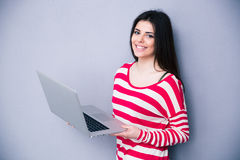 Pretty smiling woman standing with laptop Stock Photos