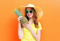 Pretty smiling woman in sunglasses and hat with pineapple over colorful orange. Background Stock Images