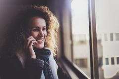 Pretty smiling woman talking with friends by her cell telephone. Bokeh and flares effect on blurred background. Pretty smiling woman talking with friends by her Royalty Free Stock Images