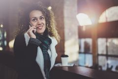 Pretty smiling woman talking with friends by her cell telephone. Bokeh and flares effect on blurred background. Pretty smiling woman talking with friends by her Royalty Free Stock Photography