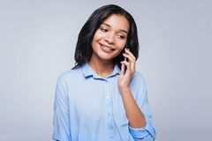 Pretty smiling woman talking on the phone. Pleasant conversation. Pretty cheerful young woman in a baby blue shirt talking on the phone and smiling while Stock Photography