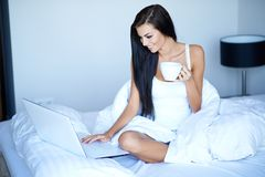 Pretty Smiling Woman Using Laptop on Bed Stock Photos