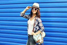 Pretty smiling woman wearing a straw hat, sunglasses and backpack Stock Photos