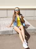 Pretty smiling woman wearing a sunglasses and jeans clothes. With backpack having fun in the city Royalty Free Stock Images