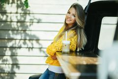 Pretty smiling woman is wearing yellow sweater drinking coffee latte near old retro bus. Young smiling woman is wearing yellow knitted sweater and jeans is Royalty Free Stock Photography