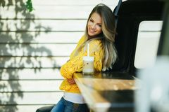 Pretty smiling woman is wearing yellow sweater drinking coffee latte near old retro bus. Young smiling woman is wearing yellow knitted sweater and jeans is Stock Image
