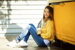 Pretty smiling woman is wearing yellow sweater drinking coffee latte near old retro bus. Young smiling woman is wearing yellow knitted sweater and jeans is Royalty Free Stock Images