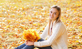 Pretty smiling woman with yellow maple leafs in autumn Royalty Free Stock Photos