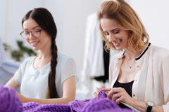 Pretty smiling women enjoying knitwork. Pleasure of creation. Two gorgeous pleasant women knitting with purple threads and seemingly enjoying themselves during Stock Image
