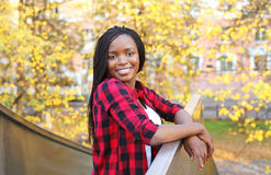 Pretty smiling young african woman wearing a red checkered shirt Royalty Free Stock Photography