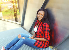 Pretty smiling young african woman wearing a red checkered shirt Royalty Free Stock Images