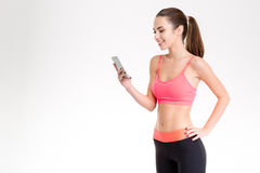 Pretty smiling young fitness woman using cellphone isolated Royalty Free Stock Photos