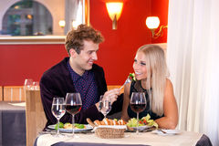 Pretty Smiling Young Lovers Date at Restaurant Stock Photos