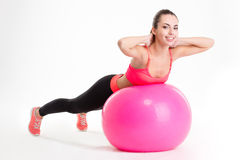 Pretty smiling young sportswoman exercising with fitball Stock Images