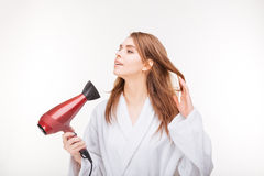 Pretty smiling young woman in bathrobe using hair dryer Stock Image