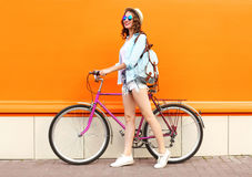Pretty smiling young woman with bicycle over colorful orange Royalty Free Stock Photos