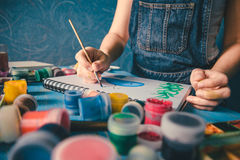 Pretty smiling young woman drawing a picture with poster paint Royalty Free Stock Images