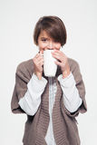 Pretty smiling young woman in knitted jacket drinking tea Stock Photos
