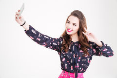 Pretty smiling young woman making selfie and showing peace sign Stock Photos
