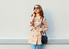 Pretty smiling young woman talking on smartphone wearing a coat and black handbag clutch stands over grey. Background Stock Photography