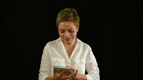 Pretty smiling young woman texting by tablet pad stock video