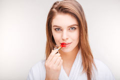 Pretty smiling young woman using lipstick on half of lips Stock Photos