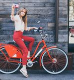Pretty smiling young woman using taking self portrait on pink vintage camera with retro bicycle over old wood planks background. Outdoor Royalty Free Stock Photos