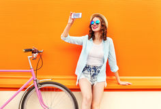 Pretty smiling young woman using taking self portrait on smartphone with retro bicycle over colorful orange Royalty Free Stock Photos