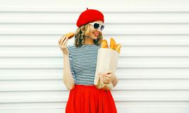 Pretty smiling young woman wearing red beret holding croissant, paper bag with a long white bread baguette on white. Wall background stock photos