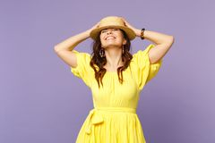 Pretty smiling young woman in yellow dress, summer hat keeping eyes closed, putting hands on head isolated on pastel stock photo