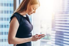 Pretty smilingwoman using smartphone standing in office.  Stock Photography