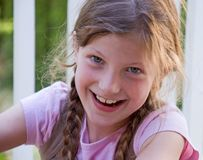 Pretty Smilng 8 Year Old Girl. Closeup photo of a pretty 8 year old Caucasian girl smiling and happy.  She's got long brown hair and braided in pig tails Royalty Free Stock Photos