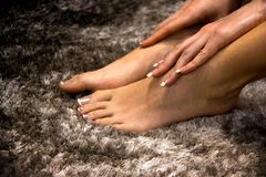 Pretty and soft woman feet touched by hands close up, white and pink transparent french manicure on her nails and toes, side view stock image