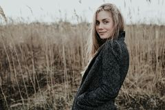 Pretty and sophisticated young woman with long blonde hair dressed in wool coat Stock Photography