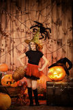 Pretty sorcery. Pretty little girl witch posing with pumpkins in halloween decorations. Halloween party Royalty Free Stock Images