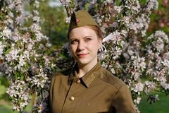 Soviet female soldier in uniform of World War II stands near flowering tree. Pretty Soviet female soldier in uniform of World War II stands near flowering tree royalty free stock photos