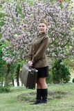 Soviet female soldier in uniform of World War II with suitcase stands on a stump near flowering tree. Pretty Soviet female soldier in uniform of World War II Royalty Free Stock Photo