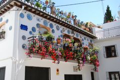 Pretty Spanish townhouse, Granada. Wrought iron balcony on a traditional Spanish townhouse with assorted flowers and decorated plates in the Albaicin District Royalty Free Stock Image