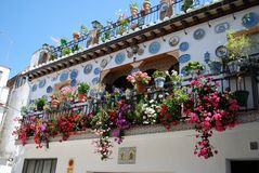 Pretty Spanish townhouse, Granada. Wrought iron balcony on a traditional Spanish townhouse with assorted flowers and decorated plates in the Albaicin District Royalty Free Stock Photo