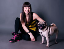 Pretty sport girl with pug dog in studio. Happy beautiful sport brunette woman sitting on the floor and holding her funny pug dog pet on a leash in studio Stock Photos