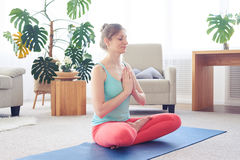 Pretty sportswoman meditating while sitting on yoga mat Royalty Free Stock Images