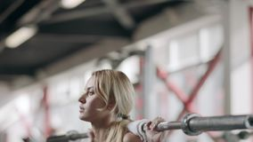 Pretty sportswoman squatting with barbell at bodybuilding training in gym. Fitness woman doing squat exercise with barbell in sport club. Strong girl having stock video footage