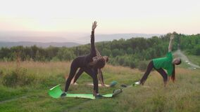 Pretty sporty fitness multiracial women stretching in yoga triangle pose on mountain top at sunrise