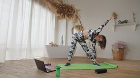 Pretty sporty fitness woman working out revolved triangle pose during online yoga class