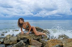 Pretty sporty girl in a dark swimsuit stand on big stone on the beach during sea ocean storm. Big waves behind her Royalty Free Stock Photography