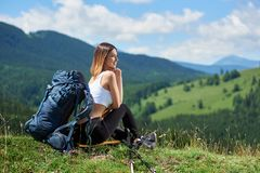 Sporty woman hiker with backpack resting in the mountains royalty free stock image