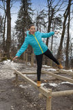Pretty sporty girl working out on balance beam Stock Photo