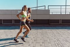 Pretty sporty woman and man jogging at city stock images