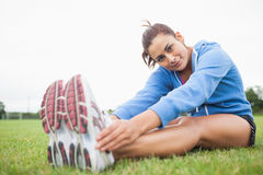 Pretty sporty woman stretching her legs while sitting on the grass Stock Photo